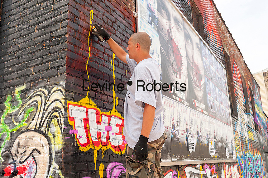 "Jerms works on his mural in Bushwick, Brooklyn in New York during the annual Bushwick Collective Block Party on Saturday, June 4, 2016. Music and partying brought some but the real attraction was the new murals  by ""graffiti"" artists that decorate the walls of the buildings that the collective uses.  (© Richard B. Levine)"
