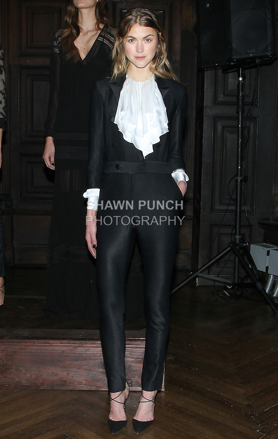 "Model Ingrid poses in a white silk washed charmeuses ruffle bib blouse and black stretch satin twill DB Tuxedo plunging N-neck jumpsuit, from the Veronica Beard Fall 2016 ""Gypsy Caravan"" collection presentation, at the Highline Hotel on February 15 2016, during New York Fashion Week Fall 2016."