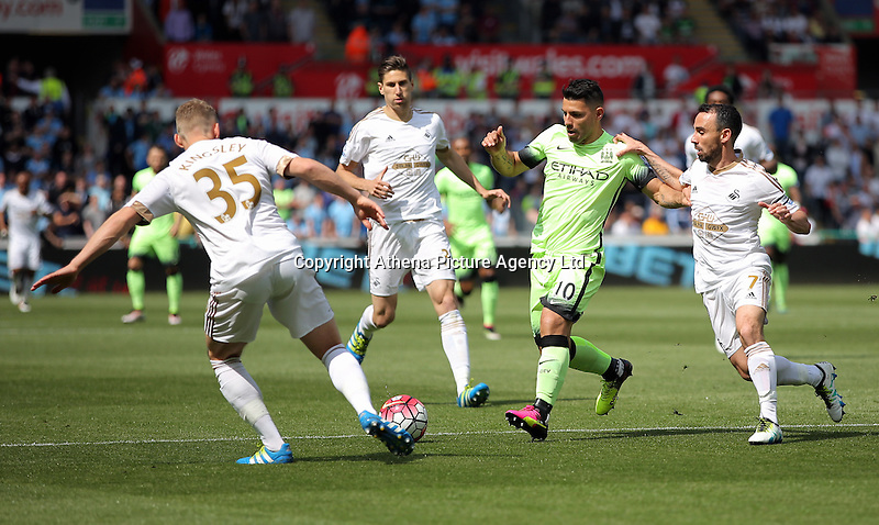 Sergio Aguero of Manchester City against ( L-R ) Stephen Kingsley (L) and Leon Britton of Swansea City (R) during the Swansea City FC v Manchester City Premier League game at the Liberty Stadium, Swansea, Wales, UK, Sunday 15 May 2016