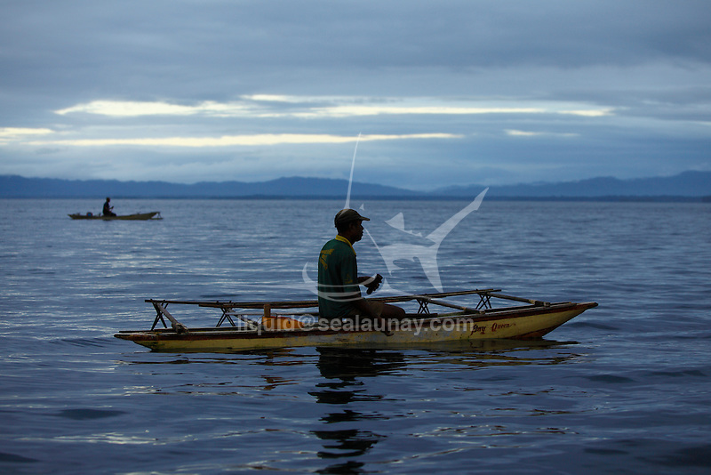 "Early morning fishermen on outrigger canoe in the Alotau Bay. Alotau is the capital of Milne Bay Province, a province of Papua New Guinea..The town is located within the area in which the invading Japanese army suffered their first land defeat in the Pacific War in 1942, before the Kokoda Track battle. A memorial park at the old battle site commemorates the event..Alotau became the provincial capital in 1969 after it was shifted from Samarai..Alotau is the gateway to the Milne Bay Province which contains some of the most remote island communities in the world. Renowned for its friendly people and amazing tropical islands, it is a very well kept secret and sees very few tourists each year. The whole of Milne bay offers some of the worlds best scuba diving and coral reef experiences..Alotau itself is a busy regional ""Outpost""-like town. Most facilities are available here although it can be sporadic at times.."