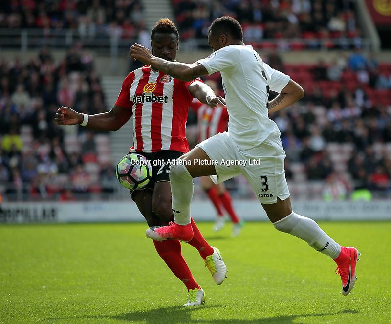 (L-R) Lamine Kone of Sunderland is challenged by Jordan Ayew of Swansea City during the Premier League match between Sunderland and Swansea City at the Stadium of Light, Sunderland, England, UK. Saturday 13 May 2017