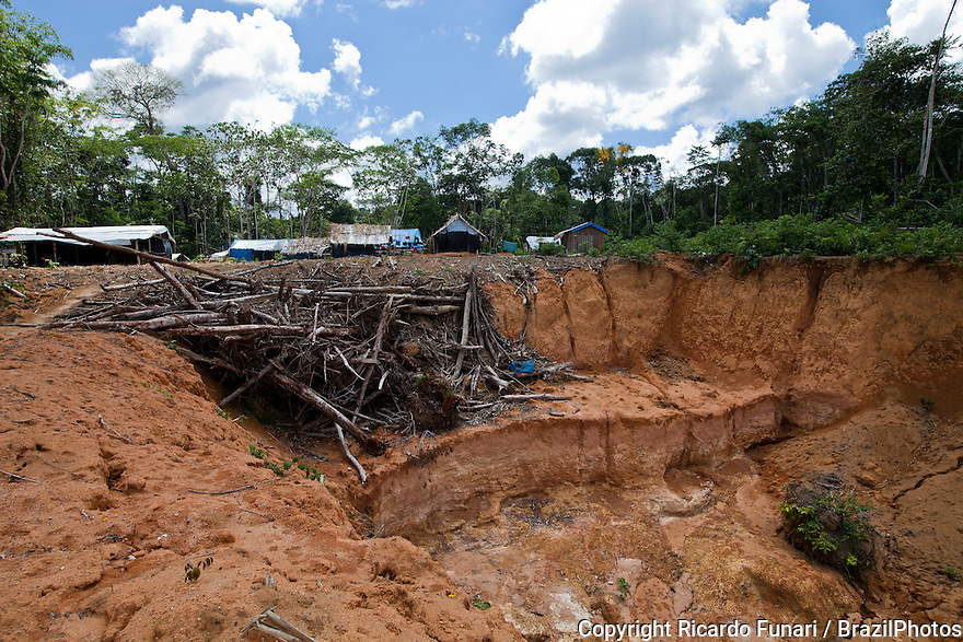 Amazon rain forest deforestation, gold miners camping area. Pit already explored. Agua Branca gold mining village, , Para State, Brazil.