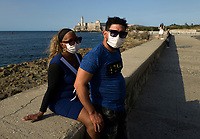 HAVANA, CUBA - MARCH 23: A cuban couple wear protective face mask as a preventive measure against the spread of the new coronavirus at the Malecon in Havana on March 23, 2020.  Thousands of tourists leave Cuba one day before the partial closure of borders announced by the Cuban Government to prevent the spread of COVID-19 becomes effective.The World Health Organization declared a global pandemic as the coronavirus rapidly spreads across the world. (Photo by Eliana Aponte/VIEWpress/Corbis via Getty Images)