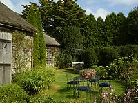 To the rear of the cottage is a pretty garden with flowers and shrubs. A metal table and chairs is set out on the lawn.