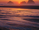 Tillamook County, OR<br /> The sun sets between Three Arch Rocks at low tide at Oceanside