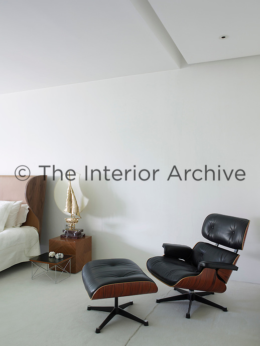 A Charles & Ray Eames leather lounge chair and footstool furnishes a corner of the master bedroom