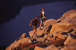 A photo of a man and woman running up a mountain in the Sierras.