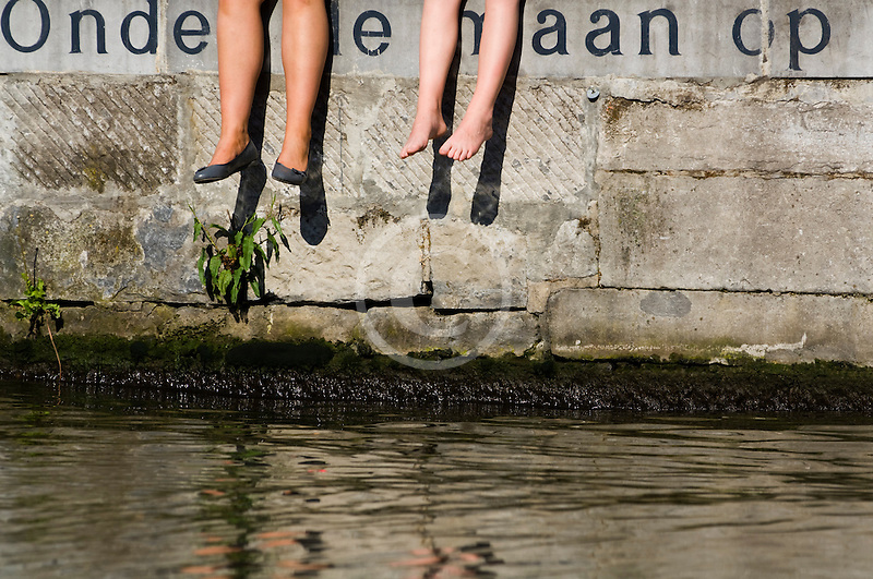 Belgium, Ghent, Students sitting alongside canal, legs only