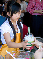 Hmong teen serving delicious three layer fruit drink. Hmong Sports Festival McMurray Field St Paul Minnesota USA