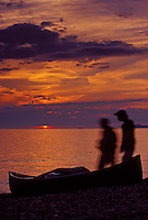 A couple walks past a canoe beached on a Lake Superior beach at sunset in Lake Superior Provincial Park near Wawa, Ontario.