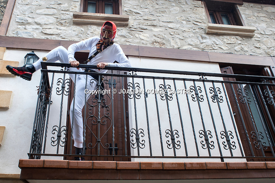 A Mamuxarro entering the balcony of a house if within some girl hides in the carnival of Unanua in Navarra.