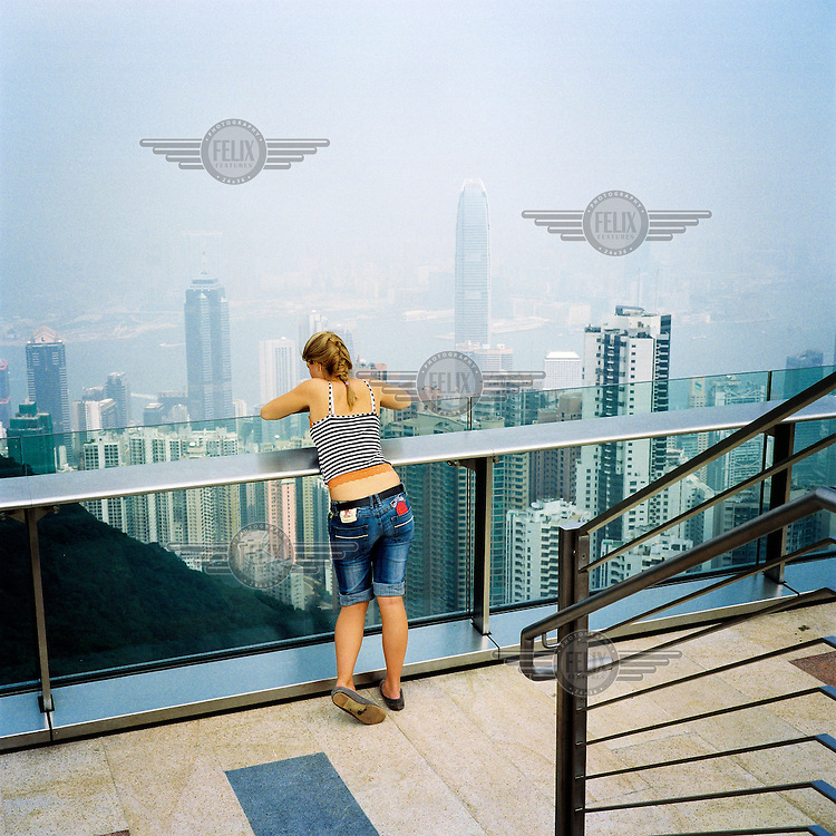 A tourist looks out over the city of Hong Kong from Victoria Peak.