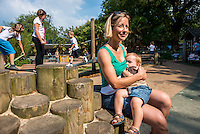 A mother breastfeeds her little boy in the playground of her local park.<br /> <br /> Hampshire, England, UK<br /> 03/09/2014<br /> <br /> &copy; Paul Carter / wdiip.co.uk