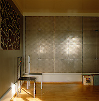 The cupboard doors which line the walls of this room are fashioned out of industrial textured aluminium and the painting is by Karl-Heinz Scherer