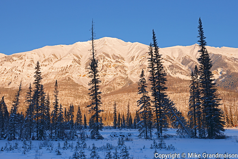 Sun setting along the Canadian Rocky Mountains at sunset, Banff National Park, Alberta, Canada
