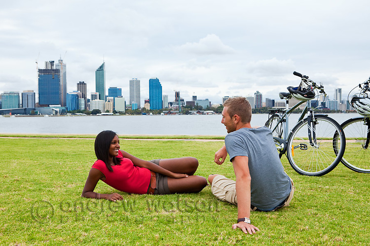 Couple relaxing on foreshore with city skyline in the background.  South Perth, Perth, Western Australia, Australia