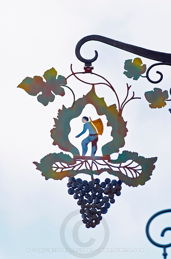 A wrought iron painted sign that illustrates the theme of champagne and wine production: a stylised vine leaf, a bunch of grapes and a man harvesting carrying a basket (hotte) on his back to collect grapes, the village of Hautvillers in Vallee de la Marne, Champagne, Marne, Ardennes, France