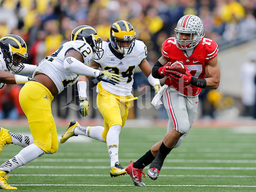 Ohio State Buckeyes running back Jalin Marshall (17) tries to get away from Michigan Wolverines linebacker Allen Gant (12) and Michigan Wolverines defensive back Delonte Hollowell (24) during the first quarter of the NCAA football game against Michigan at Ohio Stadium on Saturday, November 29, 2014. (Columbus Dispatch photo by Jonathan Quilter)