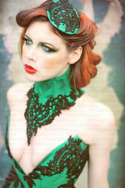 Close up of a beautiful young woman wearing an elaborate green corset and neck collar and looking seductive