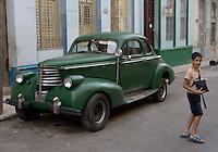 boy passing oldtimer, Havana, Cuba