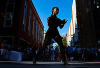 DAILY PROGRESS PHOTO/ANDREW SHURTLEFF<br /> Slivers of light outline Charlottesville Ballet member Feleacia Quezergue as she performs an original piece in remembrance of the events of August 11 & 12 during the Unity Days event Friday on the Downtown Mall.