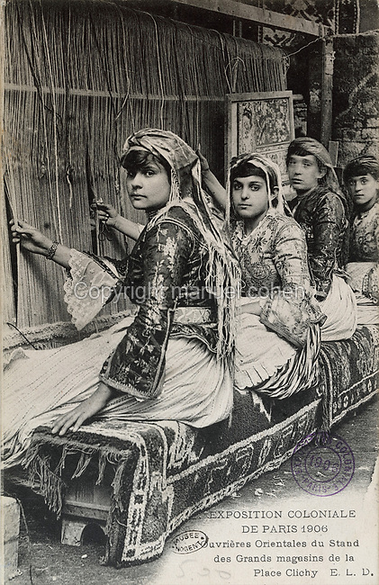 Eastern women weaving on a loom, at the stand organised by the Grands Magasins de la Place Clichy, at the Colonial Exhibition in Paris, July - November 1906, held at the Grand Palais on the Champs-Elysees, postcard from the Musee de Nogent sur Marne, Eastern Paris, France. Colonial Exhibitions were designed to increase trade with and investment in, French Overseas Territories. Picture by Manuel Cohen / Musee de Nogent sur Marne