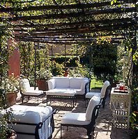 A rose covered pergola provides shade for a comfortable seating area on this garden terrace
