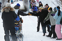Spectators cheer on Robert Nelson on the bike trail near the Native Hospital in mid-town Anchorage during the ceremonial start of the 2011 Iditarod