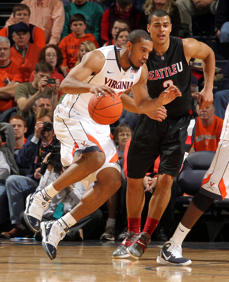 Dec. 22, 2010; Charlottesville, VA, USA;  Virginia Cavaliers forward Mike Scott (23) handles the ball in front of Seattle Redhawks forward Aaron Broussard (2) during the game at the John Paul Jones Arena. Mandatory Credit: Andrew Shurtleff