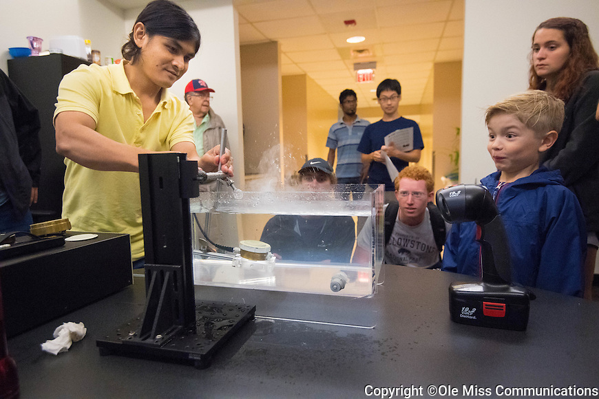 Ukesh Koju, a ph.D. student in Physics, gets a reaction from Colin Beach as he shows what sound can do to water during the open house at the NCPA's 30th anniversary celebration. Photo by Kevin Bain/Ole Miss Communications