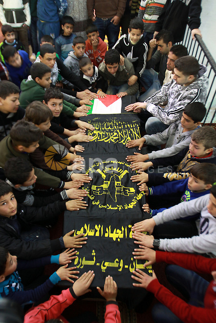 Palestinian children gather around the coffin of Abdulkareem Tahaina killed in 2002 by Israeli Army after his remains were returned in West Bank city of Jenin on Jan. 29 2014. Israel planed to return the bodies of 36 Palestinian militants buried in its foreign enemy graveyards, an Israeli official said. Photo by Nedal Eshtayah
