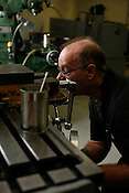 Scott Saxon, owner of the Durham TechShop, work a vertical mill at the TechShop.