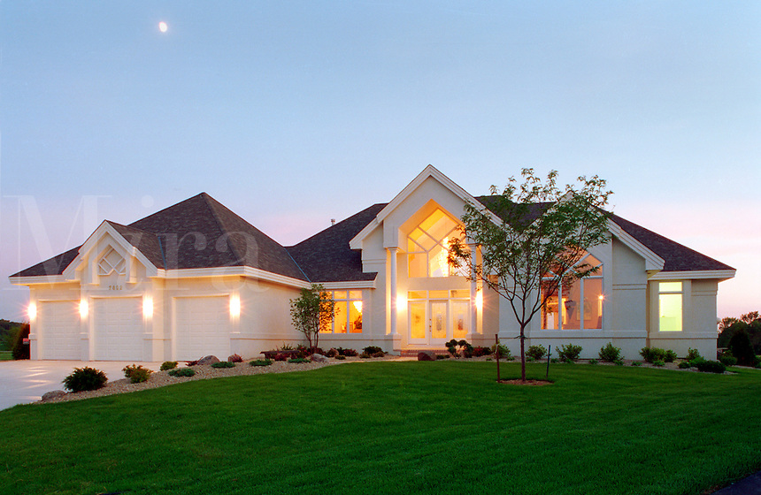 The exterior of a contemporary executive style home with the lights on at dusk.