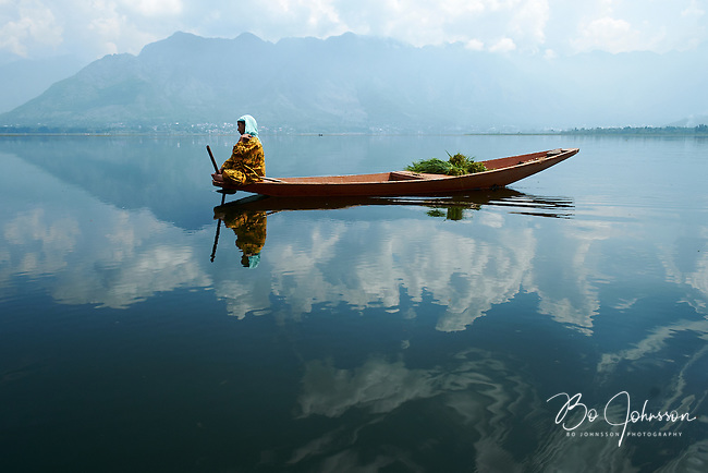 During a lazy afternoon shikara ride on the mirror calm Dal Lake in Kashmir. We were travelling from our house boat in Srinagar to the small town of Has Al Bal a few hours away. On the shore behind the lady in the shikara is the lovely Nishat Bagh Gardens from the Mughal era. Kashmir in India is a truly magical place.<br />