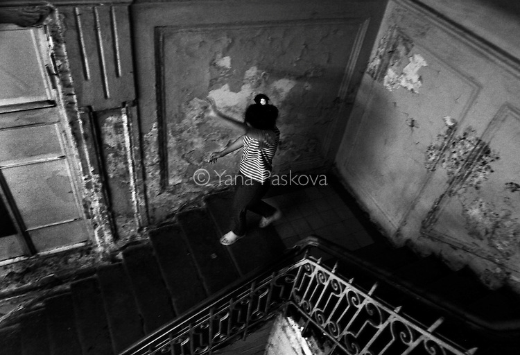 After sitting on a couch in the hallway for hours, a patient spirals down the stairs and toward the door leading out of the psychiatry ward of a county hospital in Bulgaria on August 30, 2007. A possible schizophrenic (according to the medical staff,) she rubs her face and hands repeatedly, asking whether her food is being poisoned.