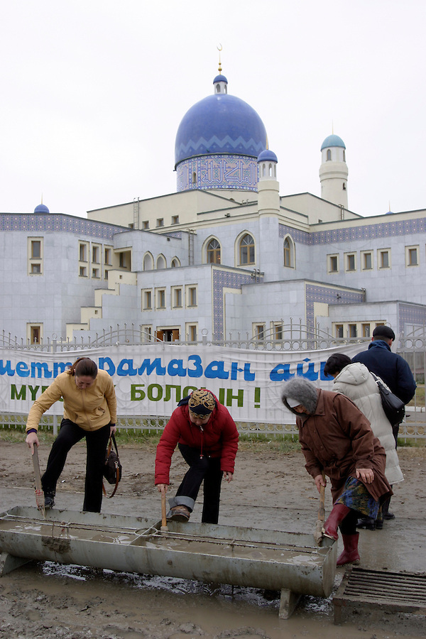 Atyrau, Kazakhstan, 14/11/2003..Worshippers clean their footwear from the mud of the streets before entering the city mosque.