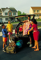 African-American family including two boys aged 9 and 13 pack suitcases and bags for holiday trip. black family.