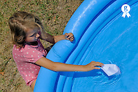 Girl (9) playing with paper boat in garden pool (Licence this image exclusively with Getty: http://www.gettyimages.com/detail/95575620 )