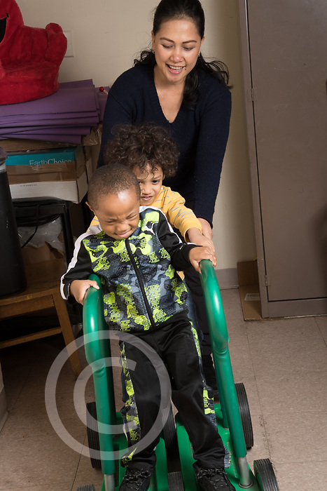 Education Preschool classroom scenes toddler-2s two boys working with occupational therapist pumping wheeled device