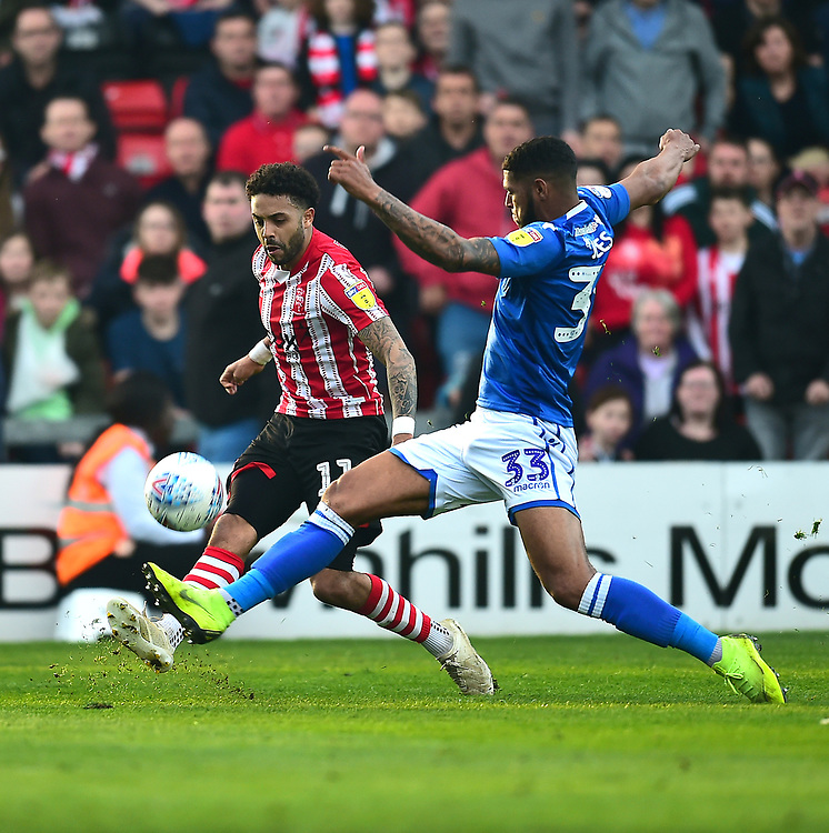 Lincoln City's Bruno Andrade crosses under pressure from  Macclesfield Town's Zak Jules<br /> <br /> Photographer Andrew Vaughan/CameraSport<br /> <br /> The EFL Sky Bet League Two - Lincoln City v Macclesfield Town - Saturday 30th March 2019 - Sincil Bank - Lincoln<br /> <br /> World Copyright © 2019 CameraSport. All rights reserved. 43 Linden Ave. Countesthorpe. Leicester. England. LE8 5PG - Tel: +44 (0) 116 277 4147 - admin@camerasport.com - www.camerasport.com