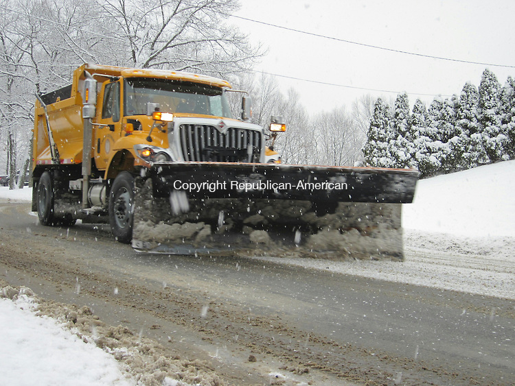 SOUTHBURY, CT - 3 Feb 2014 - 020314RH01 - A snow plow clears a path on Peter Road in Southbury. First Selectman Ed Edelson has declared a local state of emergency to allow him to buy more salt to treat the roads. Rick Harrison Republican-American