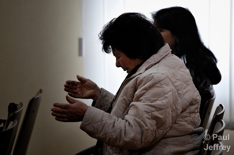 A woman prays during a worship service of the United Methodist Roma congregation in Jabuka, Serbia..