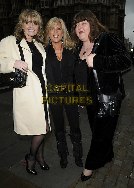 DANIELLA WESTBROOK, SAMANTHA FOX & CHERYL FERGISON.The Woman's Own Children of Courage Awards, Westminster Abbey, London, England, UK, 9th December 2009..full length white coat black trousers knee high boots suit jacket velvet jacket bag Sam patent shoes christian louboutin .CAP/CAN.©Can Nguyen/Capital Pictures