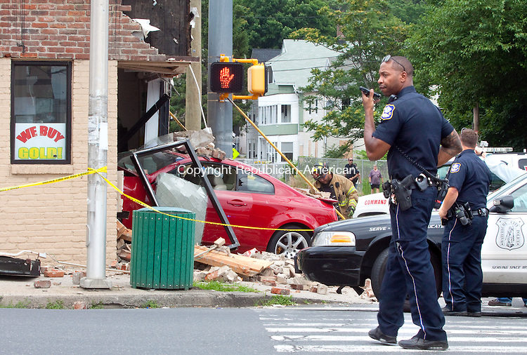 WATERBURY, CT.-03 JULY 2013 070313DA03- Waterbury officials respond on the scene of a vehicle that lost cntrol and went through National Tax Services on the corner of East Main St. and Cherry St. Wednesday afternoon. <br /> Darlene Douty Republican-American