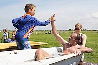 Nederland Schermerhorn  2016 07 10.  Jaarlijkse Prutmarathon door de modderige slootjes van de Mijzenpolder. Medaille winnaars worden na afloop afgesponsd in een badkuip.  Foto Berlinda van Dam / Hollandse Hoogte