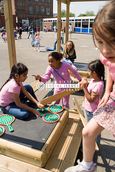 Children playing on climbing frame in school playground,