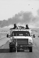 US military helicopters fly over as private security operators from the British company ArmorGroup escort a supply convoy past a burning truck on the road from Baghdad to Al Asad air base, near Iraq's border with Syria on October 22, 2006. The coalition forces and civilian administration in Iraq depend heavily on the controversial presence of thousands of private security personnel in their reconstruction efforts and military operations.