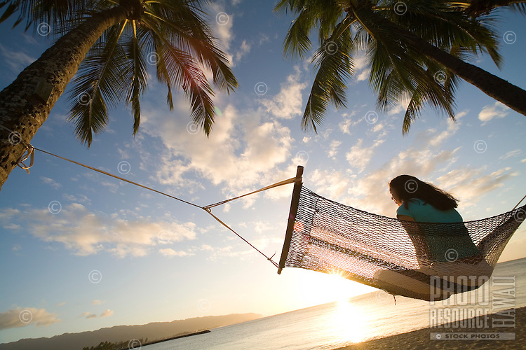 Woman relaxing in a hammock under a palm tree in the sun, Haleiwa Beach park, North Shore Oahu