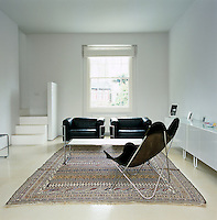A pair of Le Corbusier black leather armchairs and a leather Butterfly chair by Knoll are placed around a traditional Iranian kilim in this stark white living room