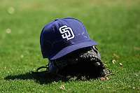 San Diego Padres hat and glove sit in the grass during an Instructional League camp day on October 4, 2016 at the Peoria Sports Complex in Peoria, Arizona.  (Mike Janes/Four Seam Images)